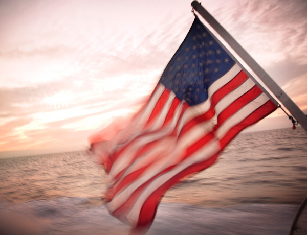 American flag blowing in the wind off the back of a boat