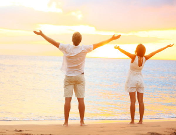 Happy cheering couple enjoying sunset at beach